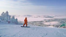 Υπόλοιπο πριν από την κάθοδο από το βουνό σε ένα σνόουμπορντ Snowboarding - κάθοδος από τις χιονισμένα κλίσεις και τα βουνά στοκ φωτογραφίες