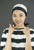 Υπόδειξη γυναικών χαμόγελου η νέα ασιατική προς τη κάμερα και από τους δύο παραδίδει τους φυλακισμένους ομοιόμορφους Στοκ εικόνες με δικαίωμα ελεύθερης χρήσης