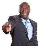 Υπόδειξη του αφρικανικού επιχειρηματία σε ένα σκοτεινό κοστούμι Στοκ Εικόνες