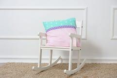 Υπόλοιπα μαξιλαριών σε μια λικνίζοντας καρέκλα στο children& x27 δωμάτιο του s Στοκ Φωτογραφίες