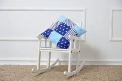 Υπόλοιπα μαξιλαριών σε μια λικνίζοντας καρέκλα στο children& x27 δωμάτιο του s Στοκ εικόνα με δικαίωμα ελεύθερης χρήσης