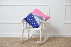 Υπόλοιπα μαξιλαριών σε μια λικνίζοντας καρέκλα στο children& x27 δωμάτιο του s Στοκ Φωτογραφία