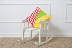 Υπόλοιπα μαξιλαριών σε μια λικνίζοντας καρέκλα στο children& x27 δωμάτιο του s Στοκ Εικόνες