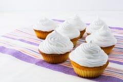 Υπόλοιπος κόσμος των άσπρων cupcakes στη ριγωτή πετσέτα λινού Στοκ Εικόνες