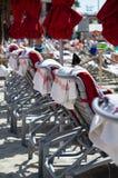 Υπόλοιπος κόσμος των αργοσχόλων παραλιών με τις πετσέτες παραλιών και τις κλειστές ομπρέλες παραλιών Στοκ Εικόνες