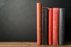 Υπόλοιπος κόσμος των βιβλίων με τις κενές σπονδυλικές στήλες στο γραφείο με τον πίνακα κιμωλίας Backgroun Στοκ Φωτογραφία