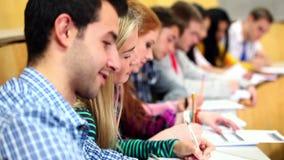 Υπόλοιπος κόσμος των ευτυχών σπουδαστών που ακούνε σε μια αίθουσα διάλεξης φιλμ μικρού μήκους
