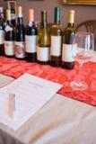 Υπόλοιπος κόσμος των μπουκαλιών κρασιού και ενός γυαλιού από ένα δοκιμάζοντας φύλλο Στοκ Εικόνες