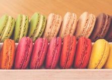 Υπόλοιπος κόσμος των παραδοσιακών γαλλικών ζωηρόχρωμων macarons στο κιβώτιο, τρύγος που τονίζεται Στοκ φωτογραφία με δικαίωμα ελεύθερης χρήσης