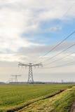 Υπόλοιπος κόσμος των πυλώνων δύναμης σε ένα αγροτικό ολλανδικό τοπίο στοκ εικόνες