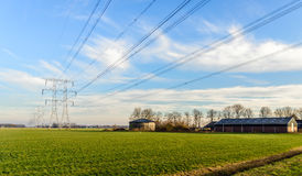 Υπόλοιπος κόσμος των πυλώνων δύναμης σε ένα ολλανδικό αγροτικό τοπίο στοκ φωτογραφία