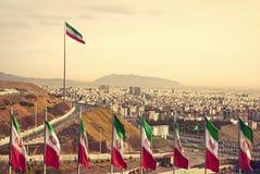 Υπόλοιπος κόσμος των σημαιών του Ιράν μπροστά από τον ορίζοντα της Τεχεράνης Στοκ εικόνα με δικαίωμα ελεύθερης χρήσης
