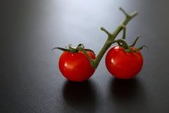 Υπόλοιπος ντομάτες κερασιών με τον πράσινο μίσχο Στοκ Φωτογραφίες