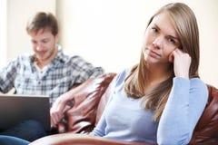 Δυστυχισμένη συνεδρίαση γυναικών στον καναπέ ως lap-top χρήσεων συνεργατών Στοκ Εικόνες