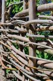 Υφαμένος ξύλινος φράκτης φιαγμένος από λεπτούς παλαιούς κλαδίσκους Στοκ Εικόνες