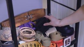 Υφαντικές ζώνες δέρματος γυναικών αφών χεριών στο ράφι στο κατάστημα απόθεμα βίντεο