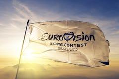 Υφαντικό ύφασμα υφασμάτων σημαιών λογότυπων διαγωνισμού 2019 τραγουδιού Eurovision που κυματίζει στη τοπ ομίχλη υδρονέφωσης ανατο ελεύθερη απεικόνιση δικαιώματος