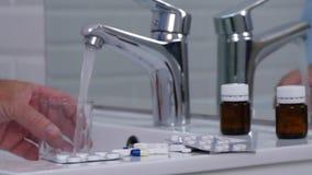 Υφισμένος το άτομο γεμίστε ένα γυαλί με το νερό και πάρτε τα χάπια ιατρικής φιλμ μικρού μήκους