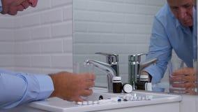 Υφισμένος το άτομο στο λουτρό γραφείων πάρτε τα χάπια με το νερό φιλμ μικρού μήκους
