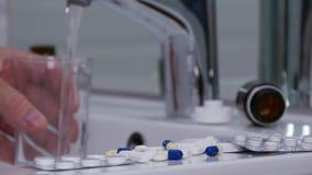 Υφισμένος το άτομο στο λουτρό πάρτε τα χάπια με ένα γυαλί με το νερό φιλμ μικρού μήκους