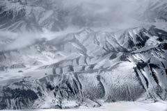 Υψηλές αλυσίδες των Ιμαλαίων το χειμώνα: οι αιχμές και οι κλίσεις καλύπτονται με το χιόνι, γύρω από τα άσπρα σύννεφα, τη γραπτή φ Στοκ φωτογραφία με δικαίωμα ελεύθερης χρήσης