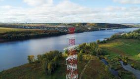 Υψηλής τάσεως εναέρια γραμμή ενάντια στην απόμακρη γέφυρα επάνω από τον ποταμό απόθεμα βίντεο