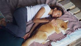 Υψηλή άποψη γωνίας της αρκετά νέας γυναίκας στις πυτζάμες και του λατρευτού ύπνου κουταβιών της μαζί στο κρεβάτι στο σπίτι Φιλία απόθεμα βίντεο