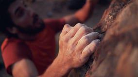 Υψηλή άποψη γωνίας του χεριού ορειβατών που αναρριχείται στον απότομο βράχο απόθεμα βίντεο