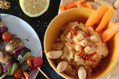 Υψηλή άποψη γωνίας του χορτοφάγου μεσογειακού γεύματος των ψημένων στη σχάρα λαχανικών και της εμβύθισης Hummus στοκ εικόνες