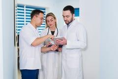 Υψηλή άποψη γωνίας τριών γιατρών στα άσπρα παλτά που έχουν τη συνομιλία στην αίθουσα νοσοκομείων Στοκ εικόνα με δικαίωμα ελεύθερης χρήσης