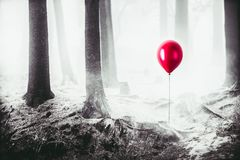 Υψηλή εικόνα αντίθεσης ενός κόκκινου μπαλονιού στα ξύλα στοκ φωτογραφία