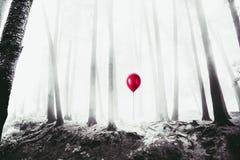 Υψηλή εικόνα αντίθεσης ενός κόκκινου μπαλονιού στα ξύλα στοκ εικόνες
