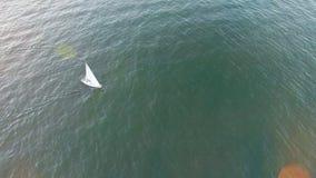 Υψηλή εναέρια άποψη γωνίας του γιοτ που κάνει τον τρόπο της μέσω των κυμάτων θάλασσας στο ηλιοβασίλεμα απόθεμα βίντεο
