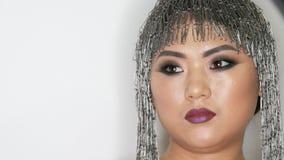 Υψηλή μόδα, πορτρέτο ενός όμορφου ασιατικού προτύπου κοριτσιών με το φωτεινό makeup και μια ασυνήθιστη περούκα των συνδετήρων χαρ απόθεμα βίντεο