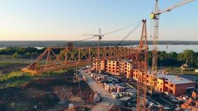 Υψηλοί γερανοί construstion σε ένα εργοτάξιο οικοδομής 4K εναέριος πυροβολισμός απόθεμα βίντεο