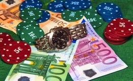 Υψηλοί πάσσαλοι κυλίνδρων σε ένα παιχνίδι πόκερ ή καρτών με τα τραπεζογραμμάτια, τα τσιπ χαρτοπαικτικών λεσχών και ένα wristwatch στοκ εικόνες με δικαίωμα ελεύθερης χρήσης