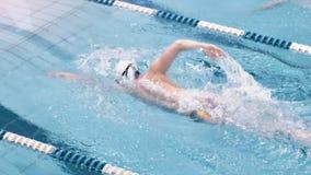 Υψηλός ευρωπαϊκός κολυμβητής γωνίας στα προστατευτικά δίοπτρα και ΚΑΠ που επιπλέει στη διαδρομή στην πισίνα απόθεμα βίντεο