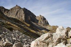 Υψηλός-ορεινοί αιχμηροί βράχοι ενάντια στο μπλε ουρανό και τα άσπρα σύννεφα Καύκασος Στοκ εικόνα με δικαίωμα ελεύθερης χρήσης