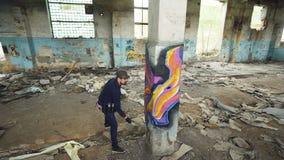 Υψηλός πυροβολισμός γωνίας του νέου αστικού ζωγράφου που δημιουργεί την αφηρημένη εικόνα στη στήλη στο παλαιό χαλασμένο κτήριο Σύ φιλμ μικρού μήκους