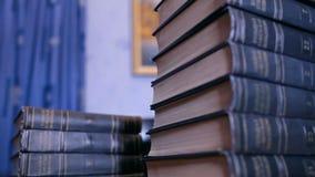 Υψηλός σωρός των βιβλίων στο γραφείο στη βιβλιοθήκη απόθεμα βίντεο