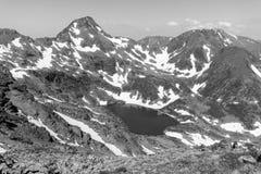 Υψηλό αλπικό τοπίο με τους τομείς και τις λίμνες χιονιού στην περιοχή Ordino Arcalis Στοκ Φωτογραφία