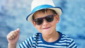 Υψηλό μικρό παιδί πορτρέτου γωνίας στενό επάνω στα γυαλιά ηλίου και καπέλο που αυξάνει τα χέρια που έχουν τη διασκέδαση υπαίθρια απόθεμα βίντεο