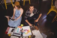 Υψηλό πορτρέτο γωνίας συνεδρίασης σχεδιαστών χαμόγελου της νέας αρσενικής από τη γυναίκα συνάδελφος με τα φύλλα Στοκ Εικόνες