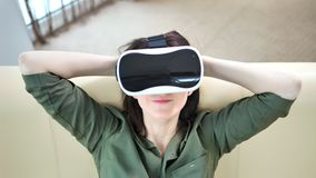 Υψηλό πορτρέτο γωνίας τοποθέτησης γυναικών χαμόγελου της νέας στα σύγχρονα γυαλιά εικονικής πραγματικότητας απόθεμα βίντεο