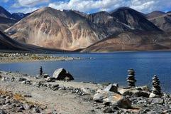 Υψηλά βουνά της λίμνης Pangong: μπλε επιφάνεια νερού, καφετιά βουνά, στο πρώτο πλάνο μια εθνική οδός και μικρά βουδιστικά stupas, Στοκ Εικόνες