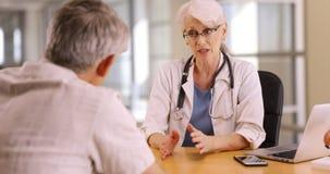 Υψηλής μόρφωσης γιατρός που συζητά τις ανησυχίες υγείας με το ηλικιωμένο άτομο στοκ εικόνες