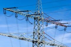 Υψηλής τάσεως πυλώνες ηλεκτρικής ενέργειας ενάντια στο μπλε ουρανό στοκ εικόνες