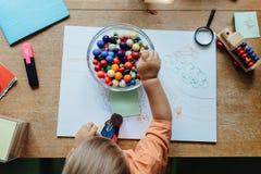Υψηλή άποψη γωνίας ενός αγοριού μικρών παιδιών που επιλέγει μια χάντρα Στοκ φωτογραφία με δικαίωμα ελεύθερης χρήσης