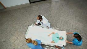 Υψηλή άποψη γωνίας μιας ομάδας νοσοκομείων που κυλά έναν ασθενή σε ένα κρεβάτι φιλμ μικρού μήκους