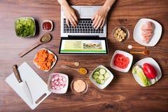 Υψηλή άποψη γωνίας της γυναίκας που χρησιμοποιεί το lap-top στην κουζίνα Στοκ εικόνες με δικαίωμα ελεύθερης χρήσης